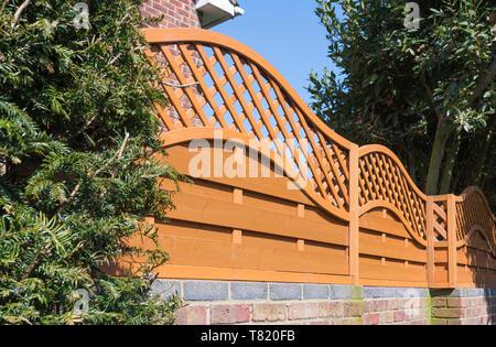 Decorative wooden fencing with diamond trellis work. - Stock Image