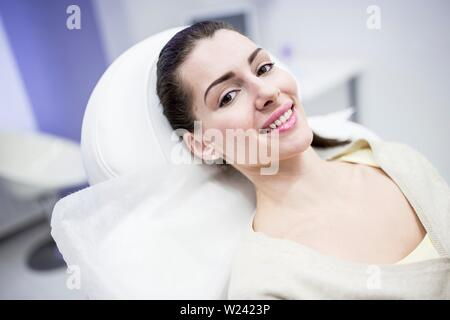 Portrait of young woman lying on couch in clinic. - Stock Image