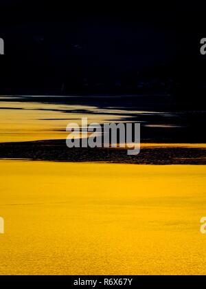 Almost golden color bright against setting sun reflection on surface of sea - Stock Image