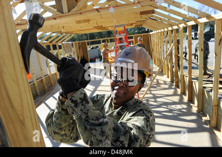 A Seabee removes nails as a hut is taken down. - Stock Image