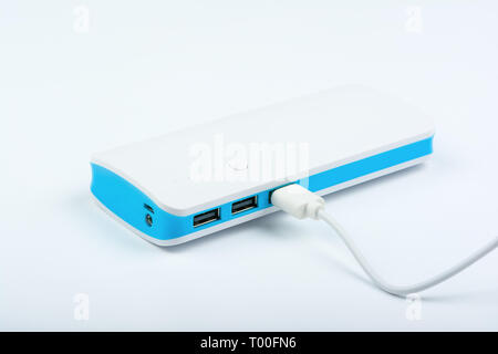 Portable power bank for charging mobile devices on white background. - Stock Image
