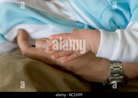 Close up from a baby hand touch adult hand together - Stock Image