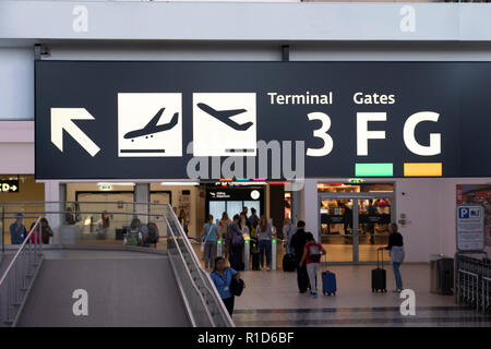 An illuminated sign at Vienna International Airport showing directions for arrivals, departures and gates - Stock Image
