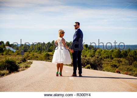 Couple of newlyweds walk along a lonely road and turn around downtown to look at camera - Stock Image