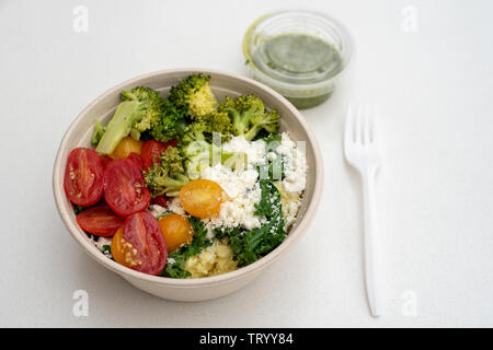 A white paper bowl with cooked and raw vegetables, garnished with feta cheese, accompanied with basil sauce on white background – vegetarian Mediterra - Stock Image