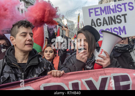 London, UK. 9th Dec, 2018. A woman holds a red smoke flare in the united counter demonstration by anti-fascists marching in opposition to Tommy Robinson's fascist pro-Brexit march. The march which included both remain and leave supporting anti-fascists gathered at the BBC to to to a rally at Downing St. Police had issued conditions on both events designed to keep the two groups well apart. Credit: Peter Marshall/Alamy Live News - Stock Image