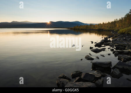 Setting sun over lake Sitojaure, near Sitojaure hut, Kungsleden trail, Lapland, Sweden - Stock Image