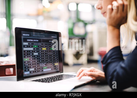 An unrecognizable industrial woman engineer in a factory using laptop. - Stock Image