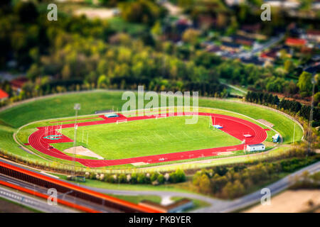 Athletic stadium seen from above with miniature objects and a grass field in the center - Stock Image