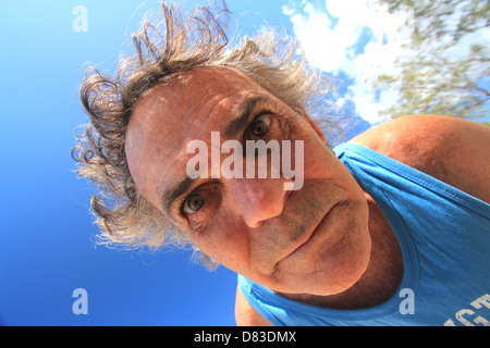 A MENTALLY ILL MAN IN HIS FIFTIES LOOKING DOWN ON A CAMERA BLUE SKY BACKGROUND HORIZONTAL BDA - Stock Image
