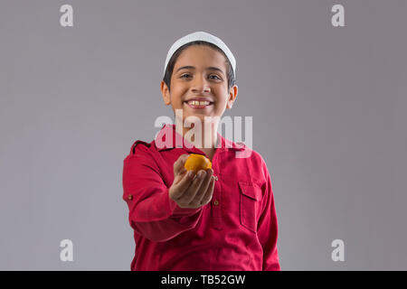 Young Muslim boy wearing cap smiling and offering sweets - Stock Image