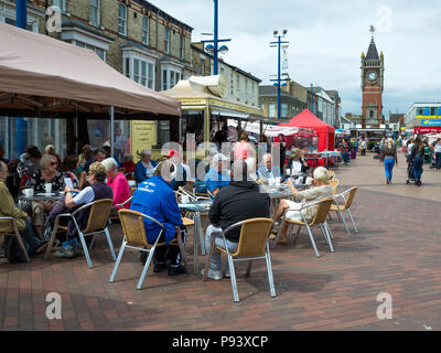 Shoppers seated at café tables at the Friday market in Redcar Cleveland North Yorkshire England UK - Stock Image