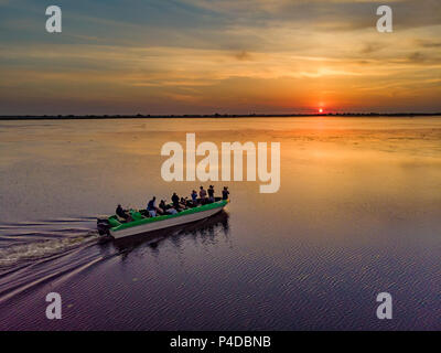 Tourists visiting Danube Delta at sunset in a motor boat. - Stock Image