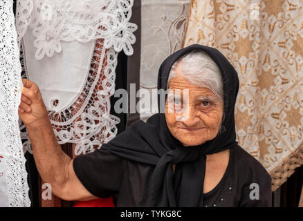 A lady selling lace at a market stall in Paphos old town, Cyprus. - Stock Image