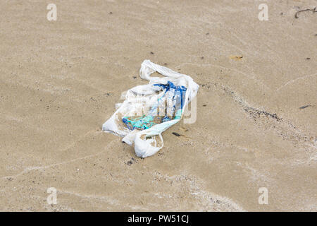 Single use plastic shopping bag washed up on a beach and part buried in the sand an example of the garbage in the oceans around the world - Stock Image