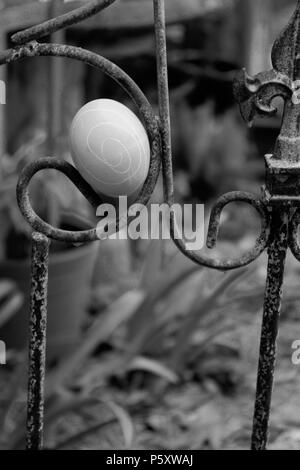 Easter Egg in iron railing Black and White - Stock Image