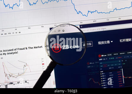 MONTREAL, CANADA - APRIL 26, 2019: ZB.com cryptocurrency digital assets exchange logo and home page on a laptop screen under magnifying glass. - Stock Image