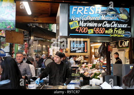 Trader selling fresh cooked hand gathered Mussels on a Borough Market seafood stall in South London England UK  KATHY DEWITT - Stock Image