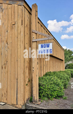 Now hiring sign hanging outside a commercial business indicating workers needed in Montgomery Alabama, USA. - Stock Image