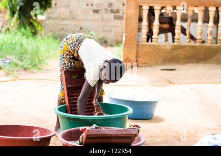 Abidjan, côte d'ivoire - February 22, 2017: young girl lowered, her hands in a basin full of dirty clothes is washing them with an instrument in front - Stock Image