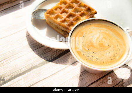 Breakfast in sunlight with vintage wooden background, white porcelain Cup with hot aromatic coffee with foam and Viennese waffle on a plate. - Stock Image