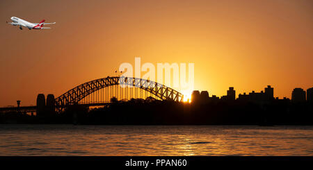 Sydney, New South Wales, Australia - October 11. 2015: Qantas passenger jet aircraft departing  with the Sydny Harbour Bridge in silhouette. - Stock Image