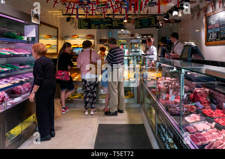 Interior of Kitson's Prize winning butchers shop in Northallerton North Yorkshire with several customers being served - Stock Image