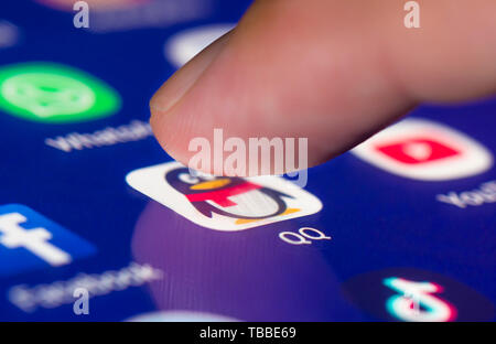 Finger pressing a shortcut icon on a smartphone or tablet touchscreen to load the Tencent QQ social media messaging app. - Stock Image