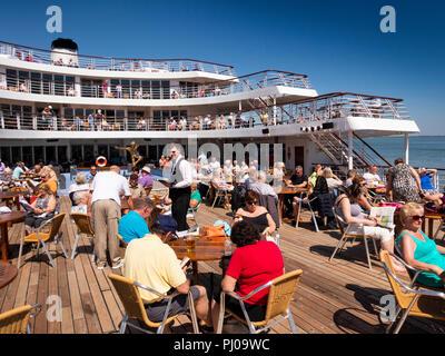 Portugal, MV Marco Polo passengers enjoying sunshine on pool deck, departing Lisbon, - Stock Image