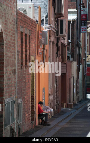 A man sits reading, alone, in a doorway on Waratah Place, a Chinatown laneway between Lonsdale and Little Bourke Streets, Melbourne - Stock Image
