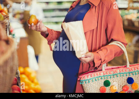 Pregnant woman shopping for apples in grocery store - Stock Image