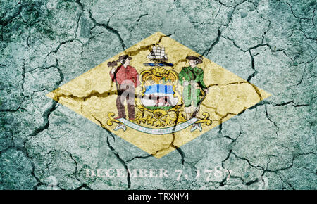 State of Delaware flag, state located in the Mid-Atlantic region of the United States, on dry earth ground texture background - Stock Image