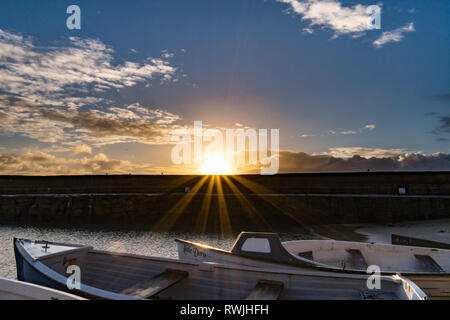 The sun rising over the harbour wall at Mousehole  in the foreground boats - Stock Image