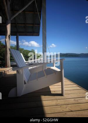 White wooden chair on a wooden verandah looking out onto blue water - Stock Image