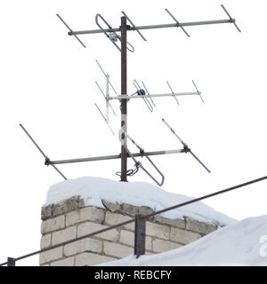 TV and communication aerials on snowy roof of residential house, multiple isolated dvb-t antennas winter scene, large detailed vertical closeup, rusty - Stock Image