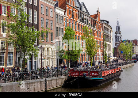 The Singel canal with the Munttoren tower in the background in Amsterdam, Netherlands - Stock Image