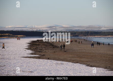 People walking on West Sands beach St Andrews with distant snow covered peaks in the Angus Glens St Andrews Fife Scotland  February 2019 - Stock Image