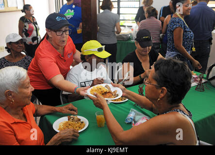 Volunteer Aileen Lopez hands out plates filled with traditional Puerto Rican Thanksgiving food inside the Centro - Stock Image