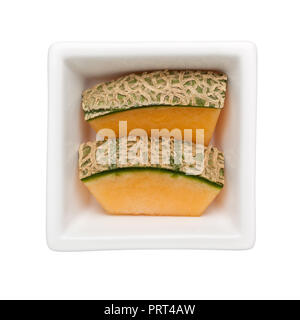 Slices of rock melon in a square bowl isolated on white background - Stock Image
