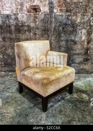Old vintage armchair in an abandoned building - Stock Image