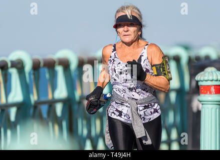 Senior woman jogging on a Spring morning in Brighton, East Sussex, England, UK. Elderly lady exercising and keeping fit. - Stock Image