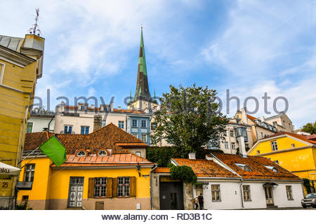 The spire of the medieval St. Olaf's Church rises above the village lining the ancient walls of the Baltic city of Tallinn, Estonia. - Stock Image