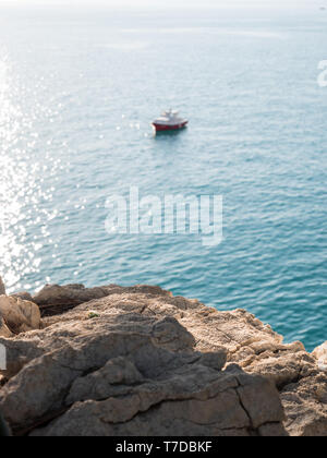 Rocky coastline and blurred boat on calm sea on sunny day - Stock Image