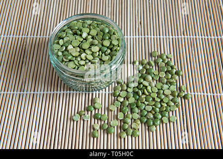 Split Green Peas slilt out of green glass jar into placemat - Stock Image