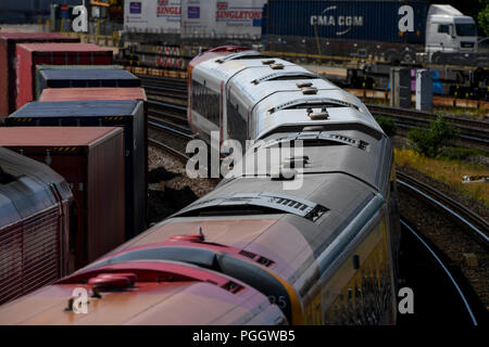 A south Western railway train passes a container train on the main line travelling towards Southampton. - Stock Image