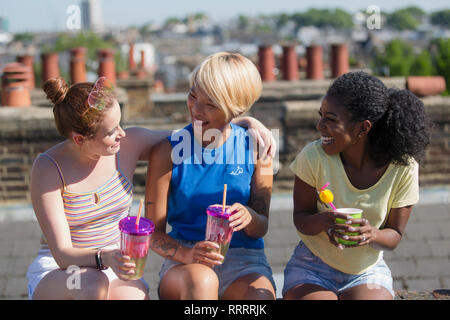 Young women friends bonding, drinking on sunny summer rooftop - Stock Image