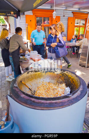 Preparation and selling of Plov, rice based Central Asian dish, Restaurant Maja, Kalnciema kvartals, Riga, Latvia - Stock Image