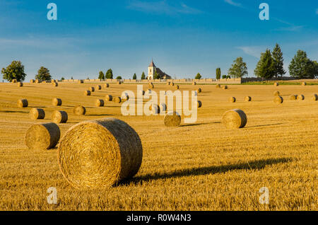 Romantic view. Straw bales field. Sunlit summer landscape. Church and churchyard on horizon. Scenic background. Golden stubble, blue sky, green trees. - Stock Image