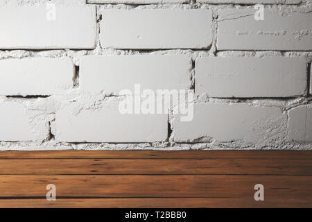 old plank wooden floor with white brick wall - Stock Image