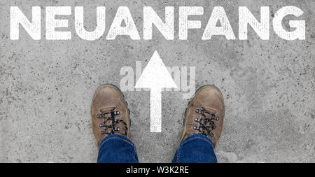 Neuanfang (German for: new start) as a word in front of feet on the road as a startup concept - Stock Image